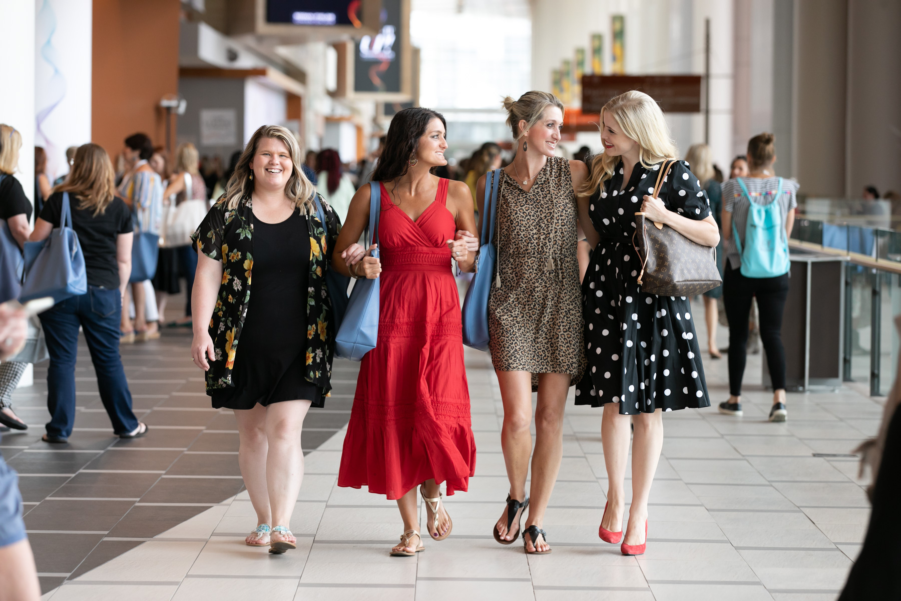 Four women walk towards Margo Moritz while engaged in conversation at a convention