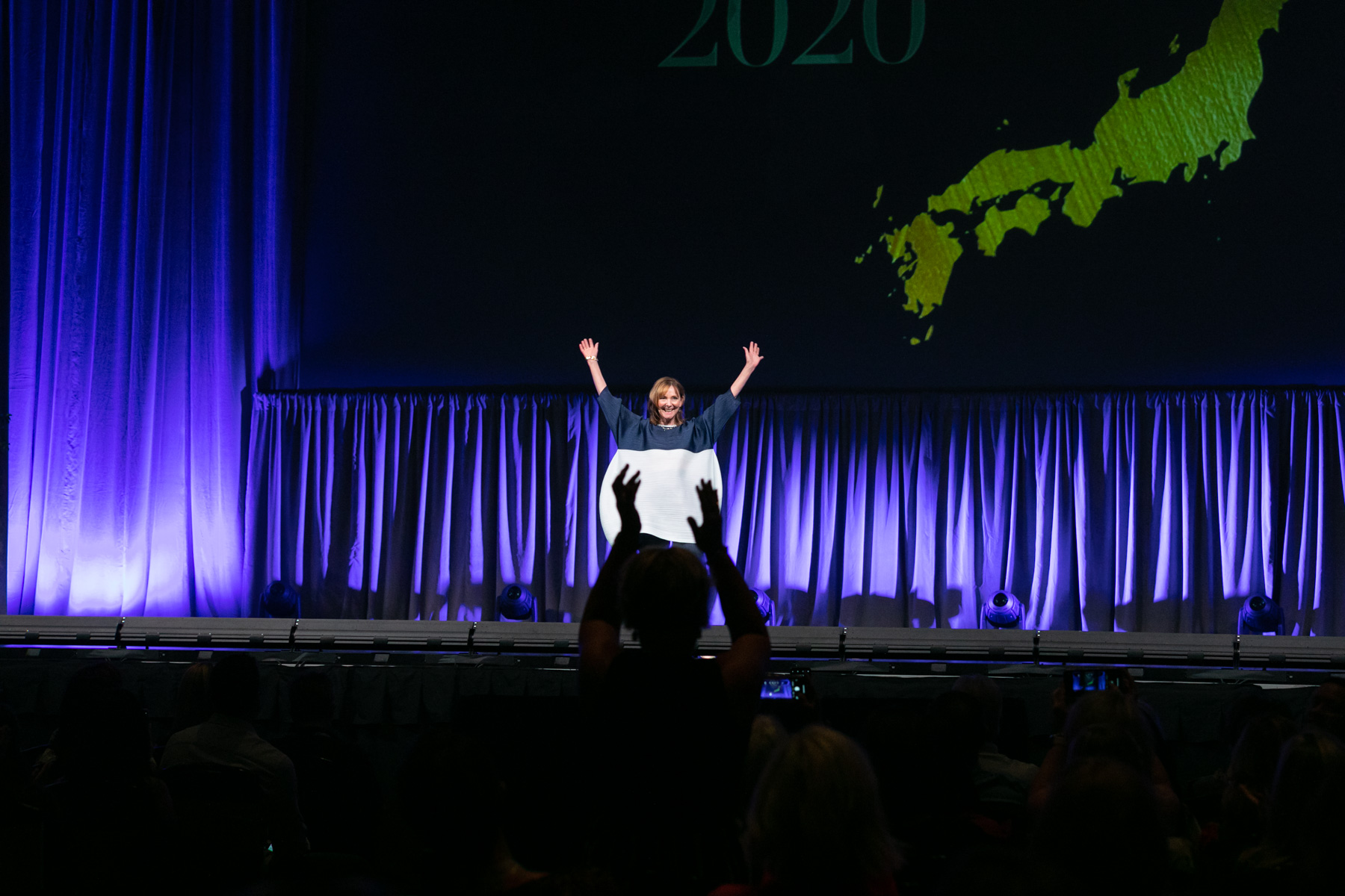 Margo Moritz captures a speaker onstage raising her hands in the air, shadowed by an audience member making a similar gesture