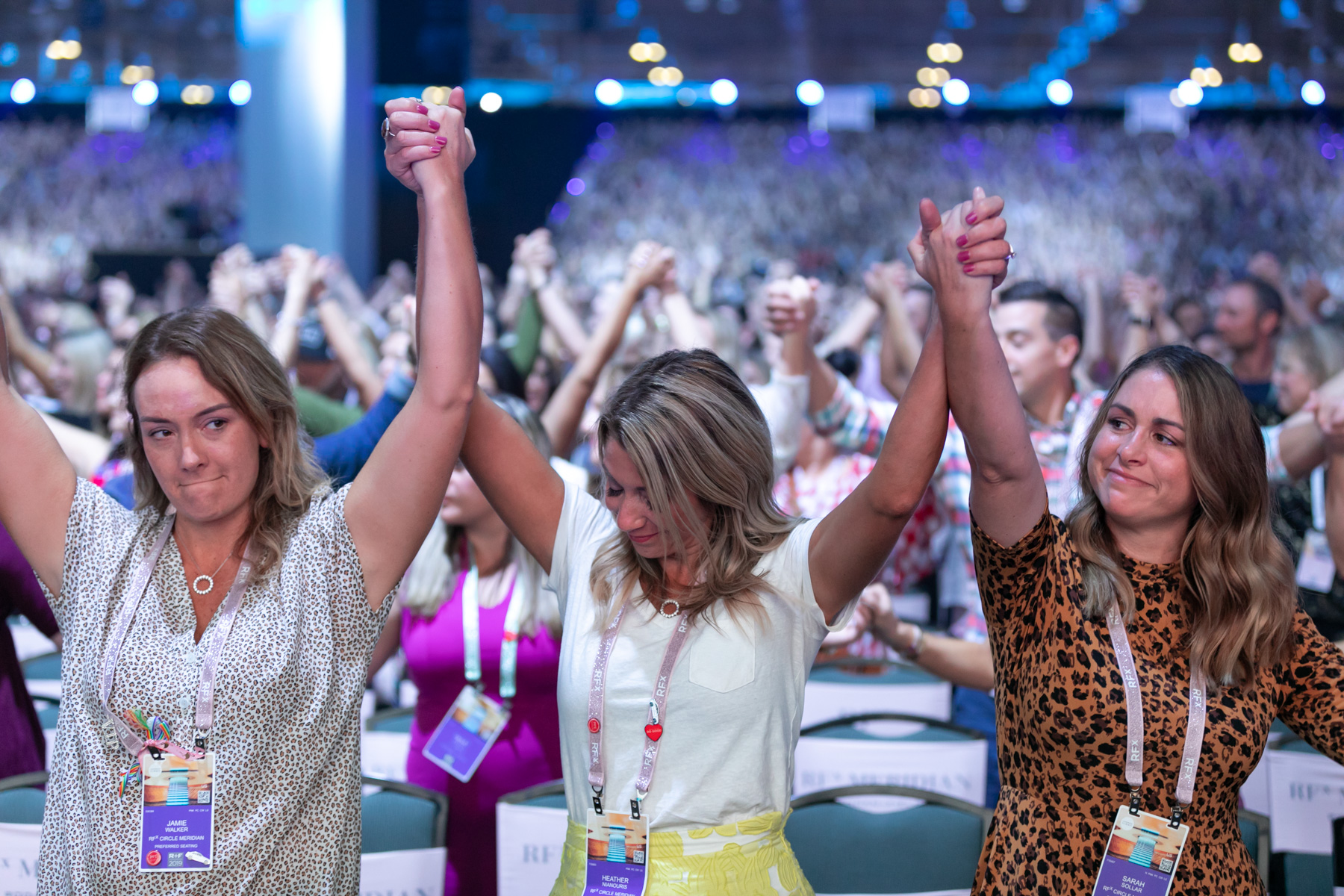 Margo Moritz captures three women with hands clasped together and raised in the air in a large crowd of convention attendees