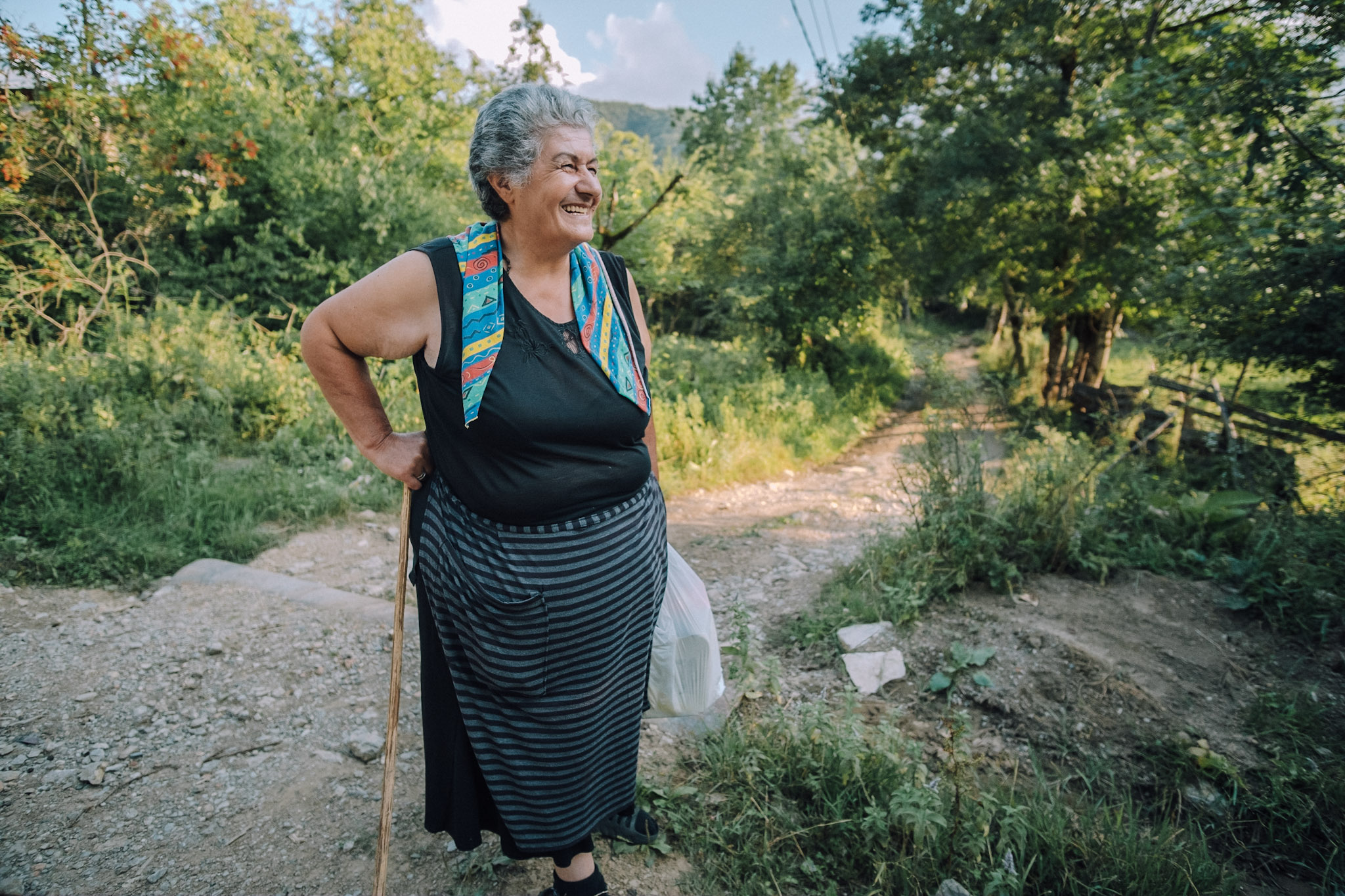 Dimitri Mais' snapshot of an older woman in Georgia, smiling, holding a plastic shopping bag and walking stick