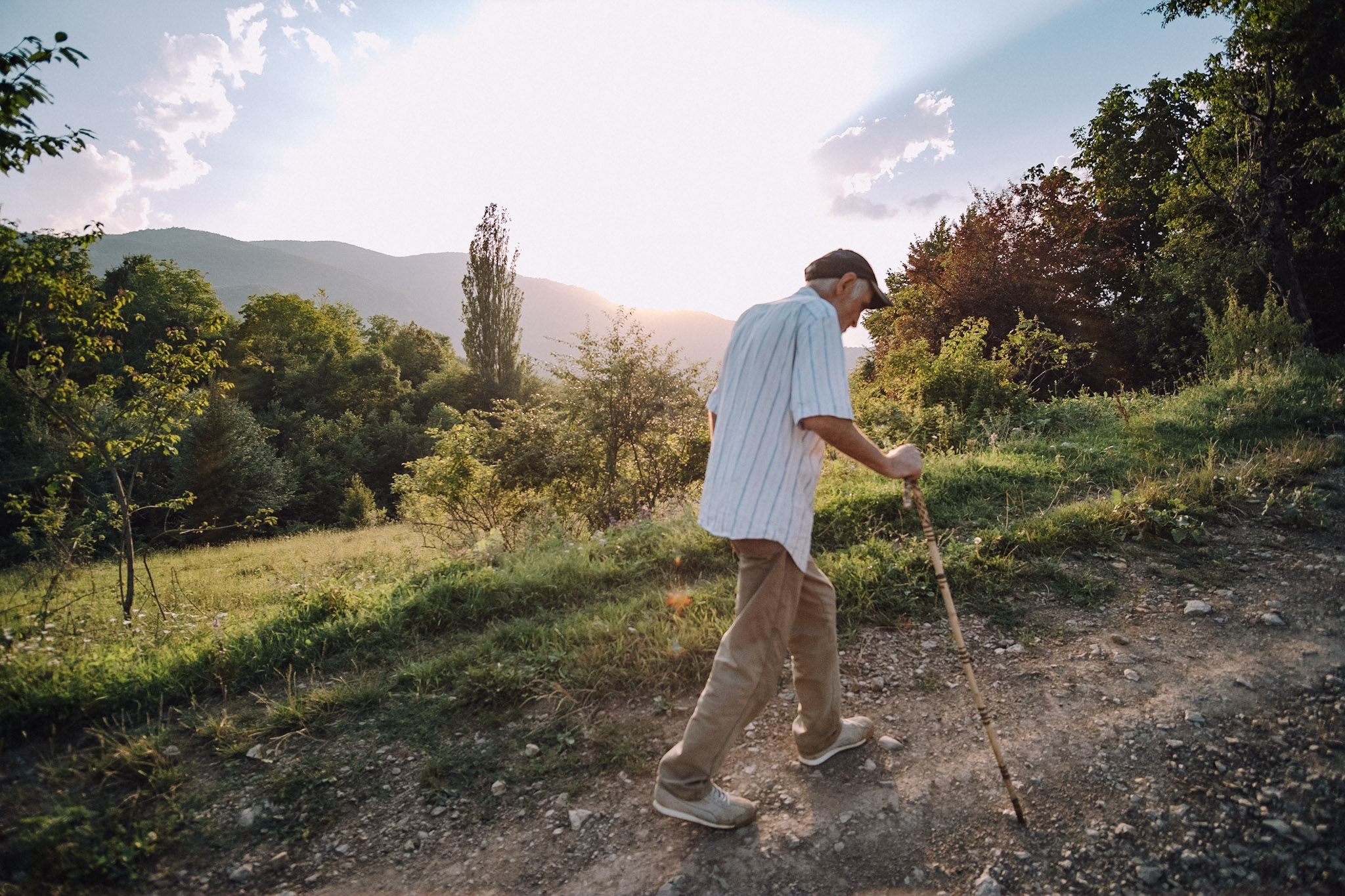Paata is shown walking a path up a hill using a walking stick in this photo by Dimitri Mais