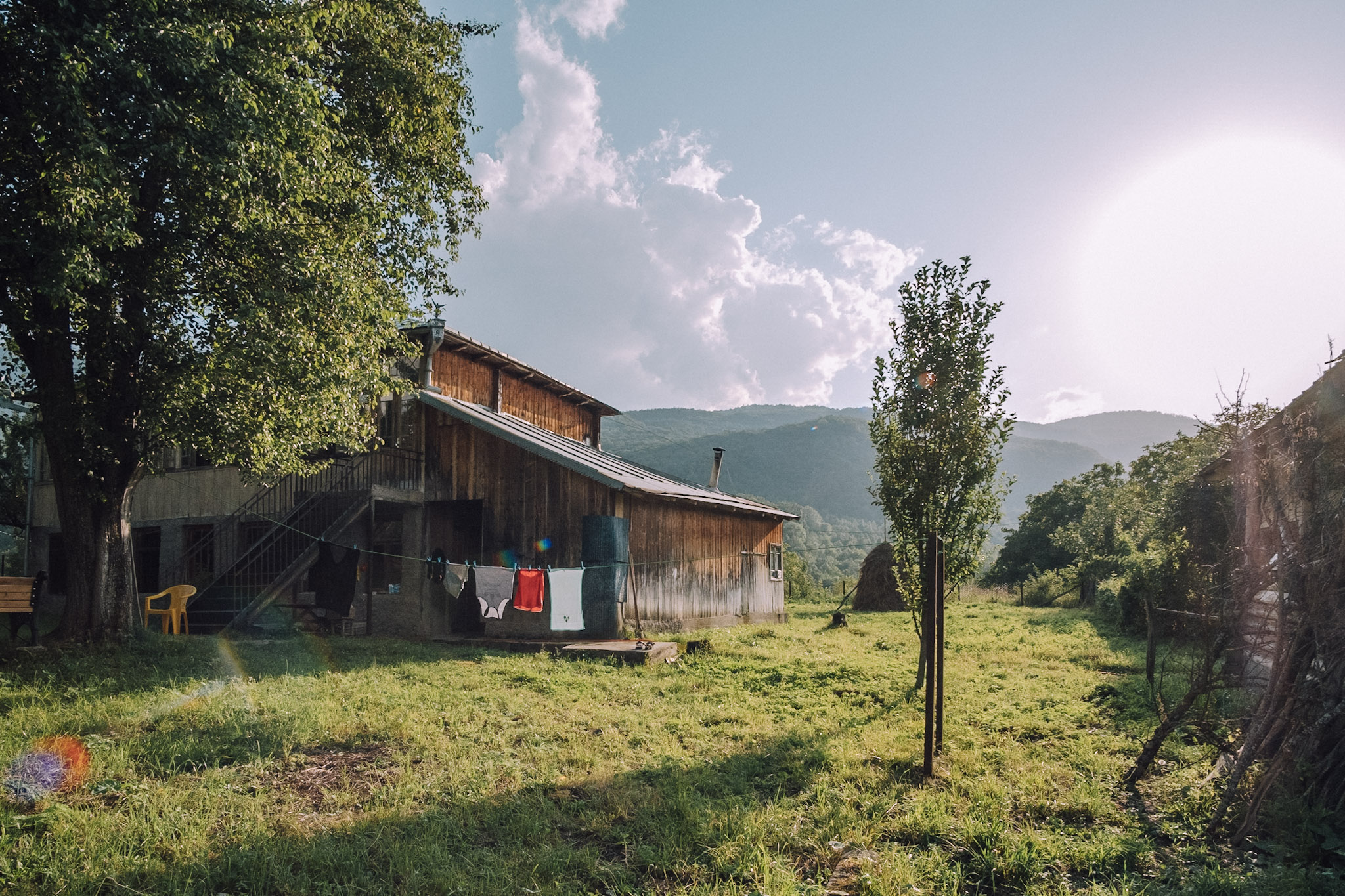 A Georgian farmhouse is set against a mountain range on a sunny day in this  landscape photo by Dimitri Mais