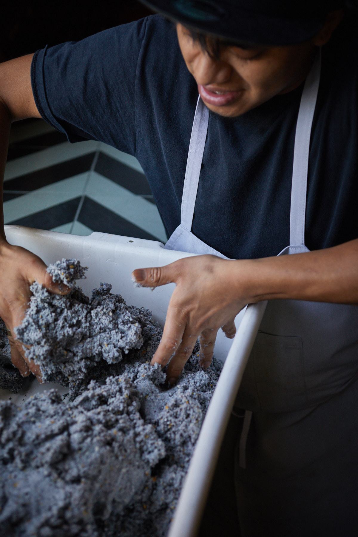 Jody Horton snaps a shot of a kitchen employee mixing blue corn masa with his hands in a large tray