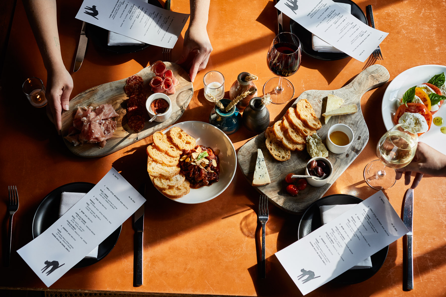 Jody Horton's shot from above as a server lays a tray of food on a table set for four