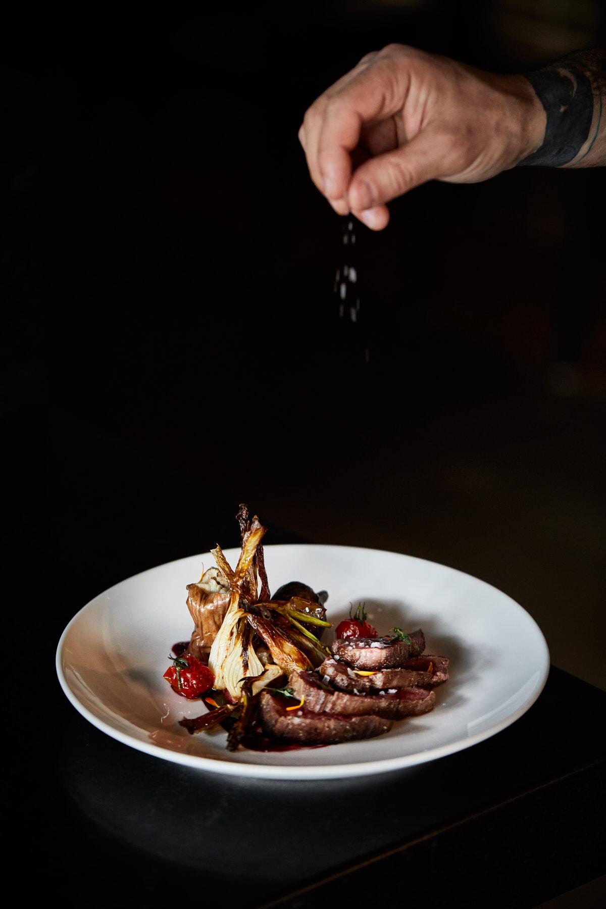 Jody Horton snaps a photo of a hand sprinkling salt on a finished dish