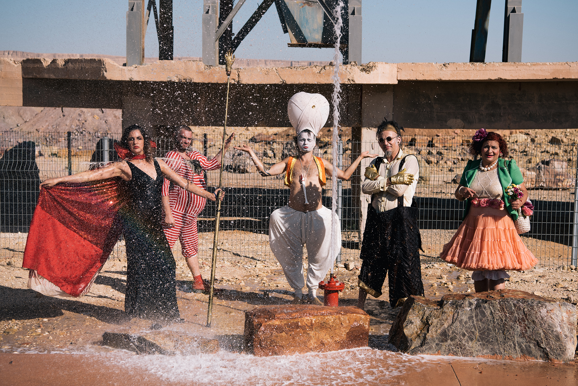 Arik Shraga and DAVAI Theater group in the dry sand as water spurts up from a fire hydrant