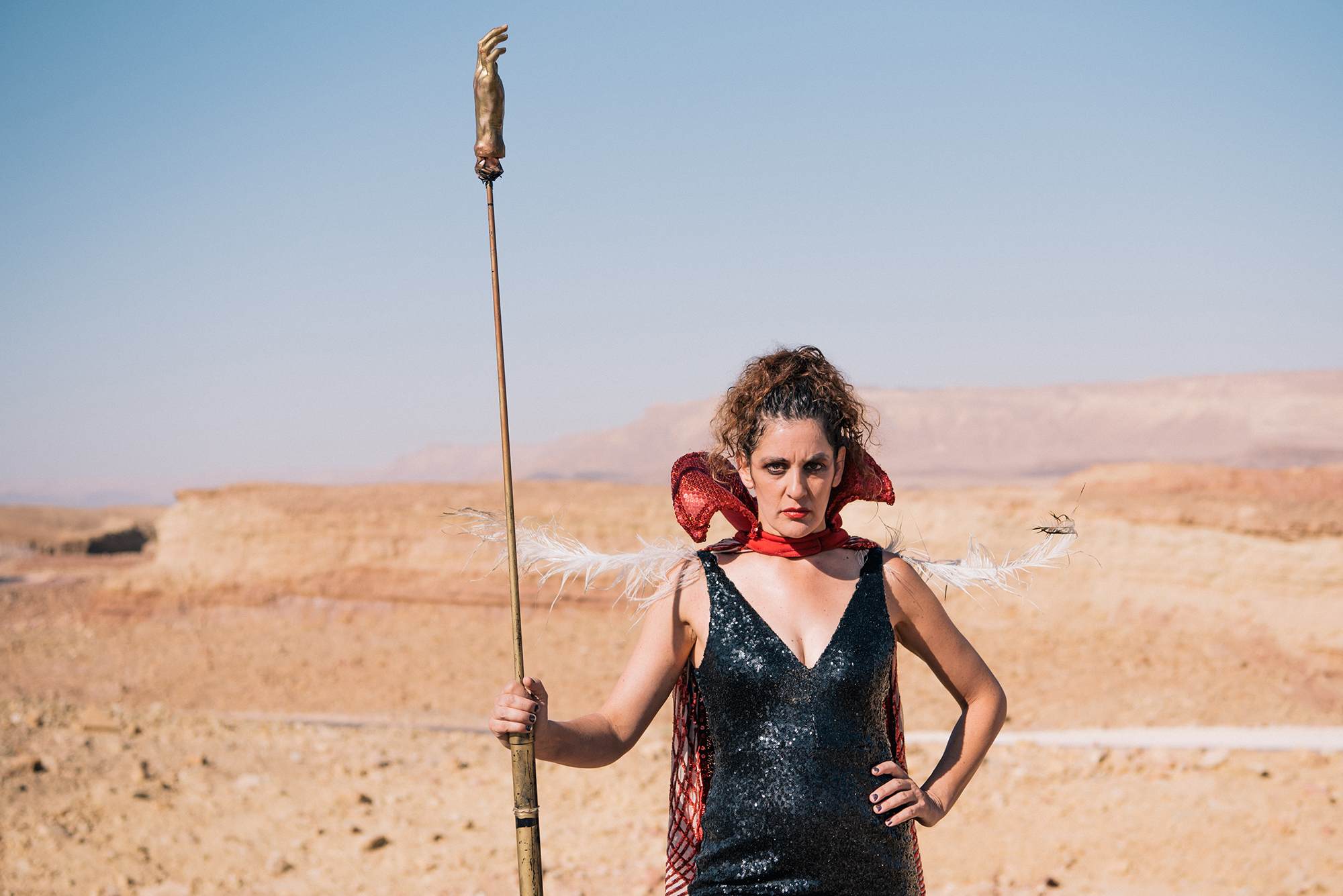 Arik Shraga photographs clown Michal Svironi looking furiously powerful in the desert with a long golden hand