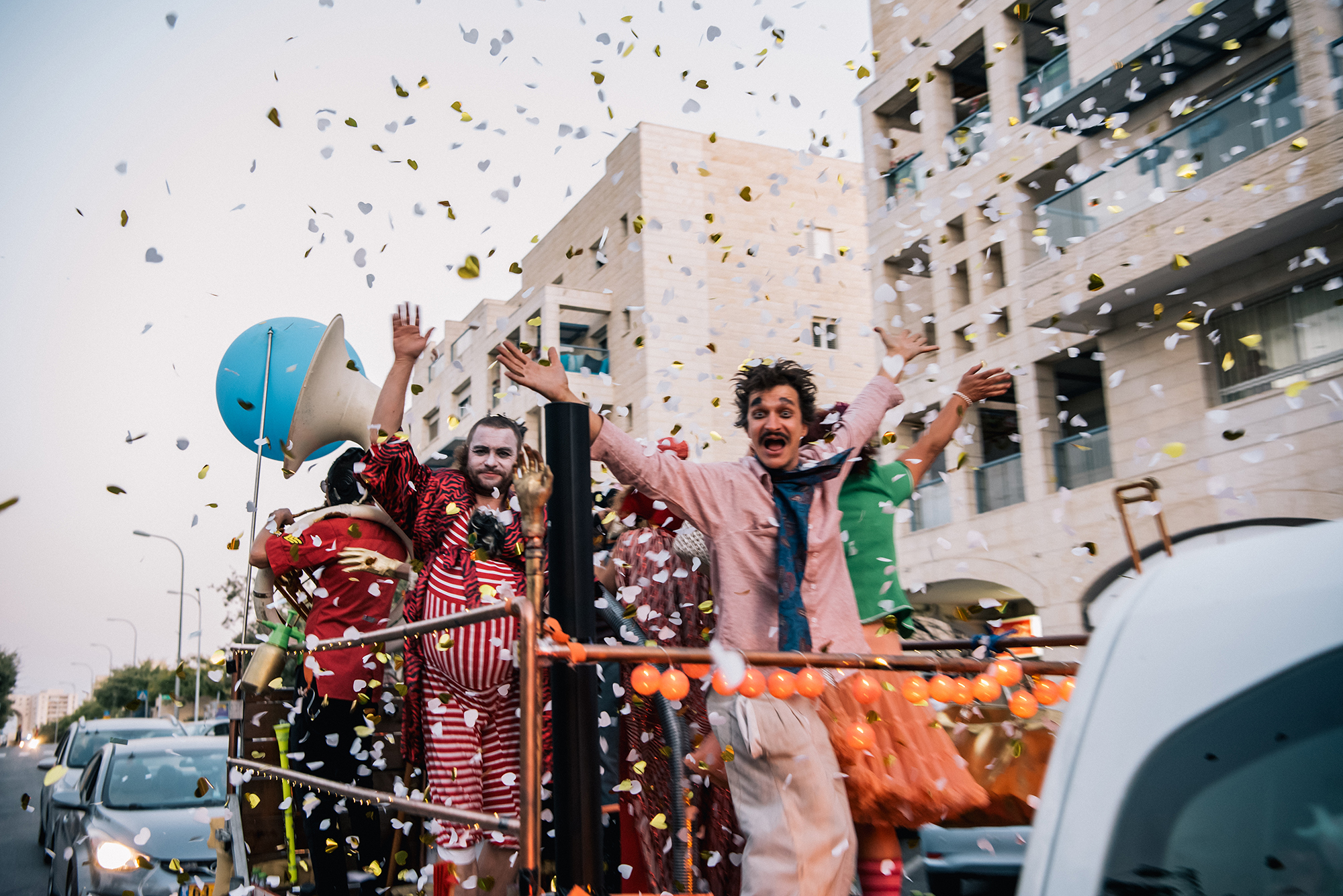 Arik Shraga photographs the DAVAI Theater group as they move down the street in their trailer as confetti falls from the sky