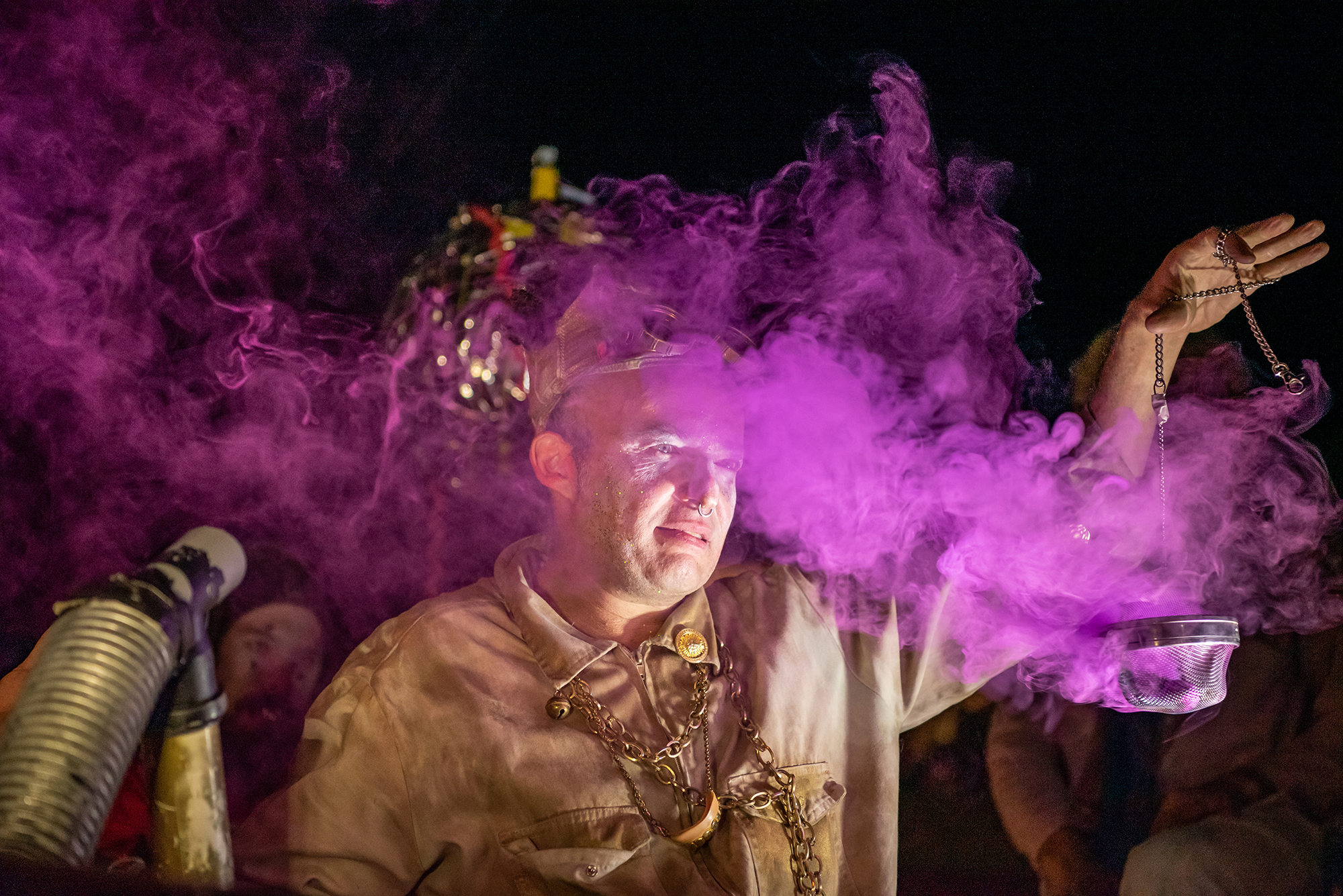 Arik Shraga Photographs a man shrouded in a mysterious purple smoke during a performance by DAVAI Theater Group