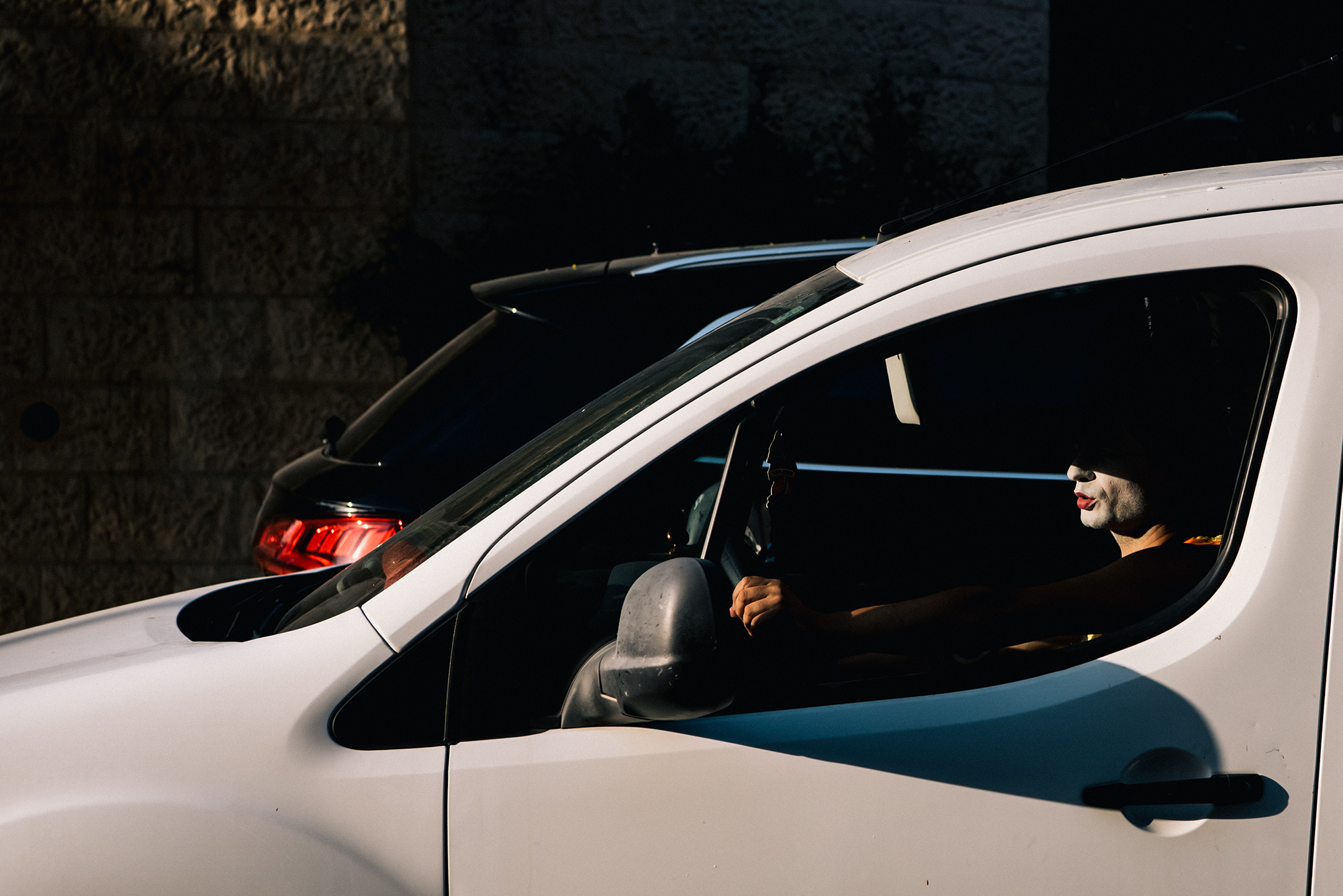Arik Shraga photographs a man in a car his face shielded except for his very red lips and jawline painted white