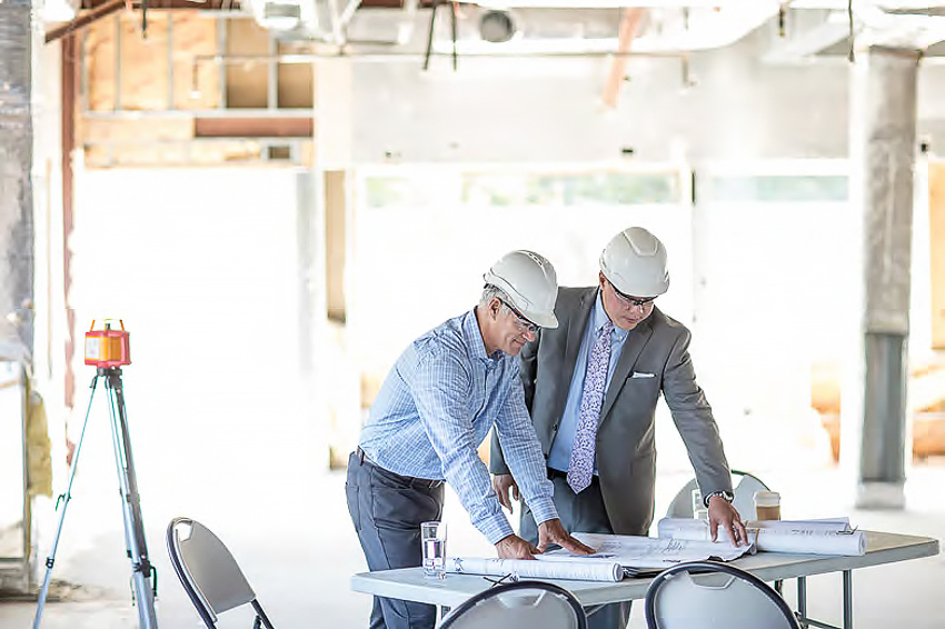 Two men in hard hats on an interior construction site looking at blueprints