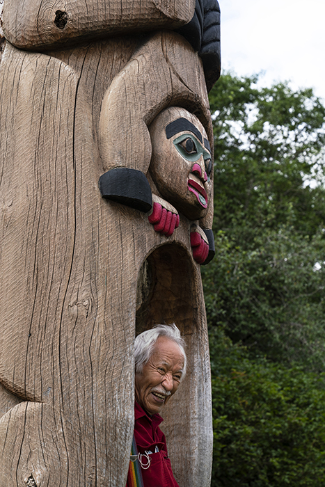 Artist at the bottom of a totem pole. Photography by Fernando Decillis for Smithsonian Magazine.