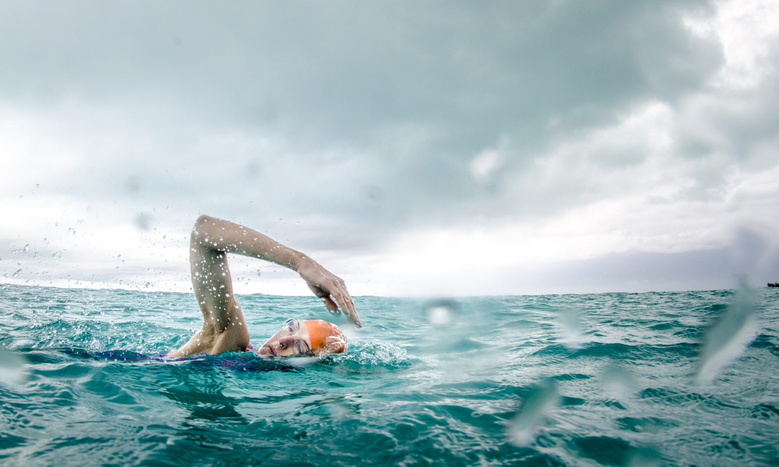 """Heather Perry's """"underwater"""" image featuring a swimmer in a storm in what looks like an ocean with crystal clear blue waters for SwimVacation"""