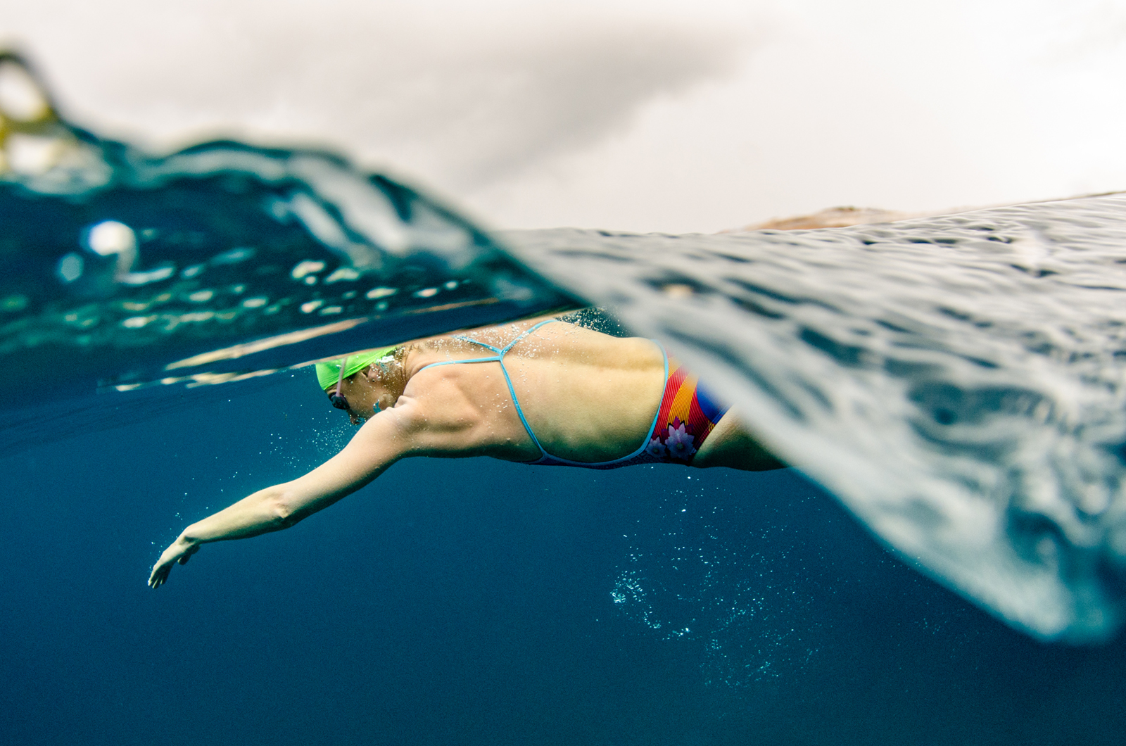 Heather Perry's underwater image is a half in the water half out shot of a swimmer doing the breaststroke with clouds looming overhead