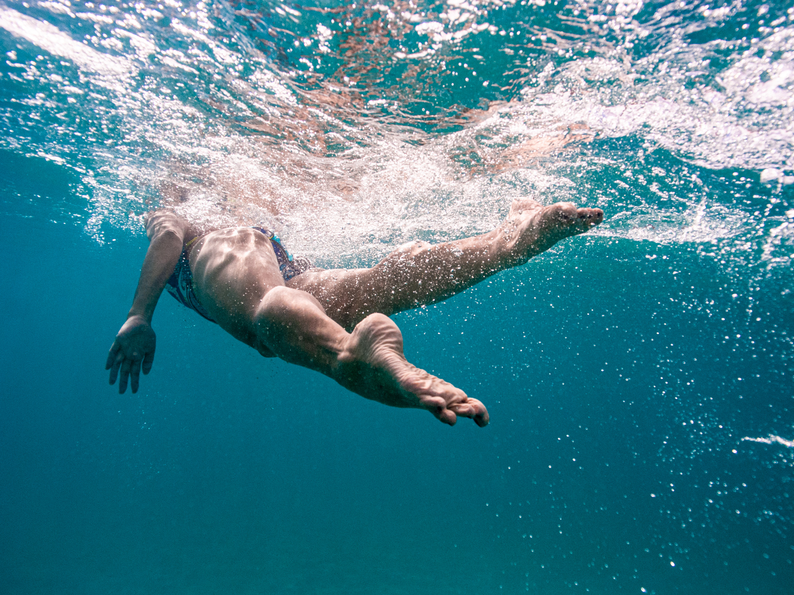 Heather Perry's underwater image from below and behind a swimmer with the light bouncing through the water and bubbles