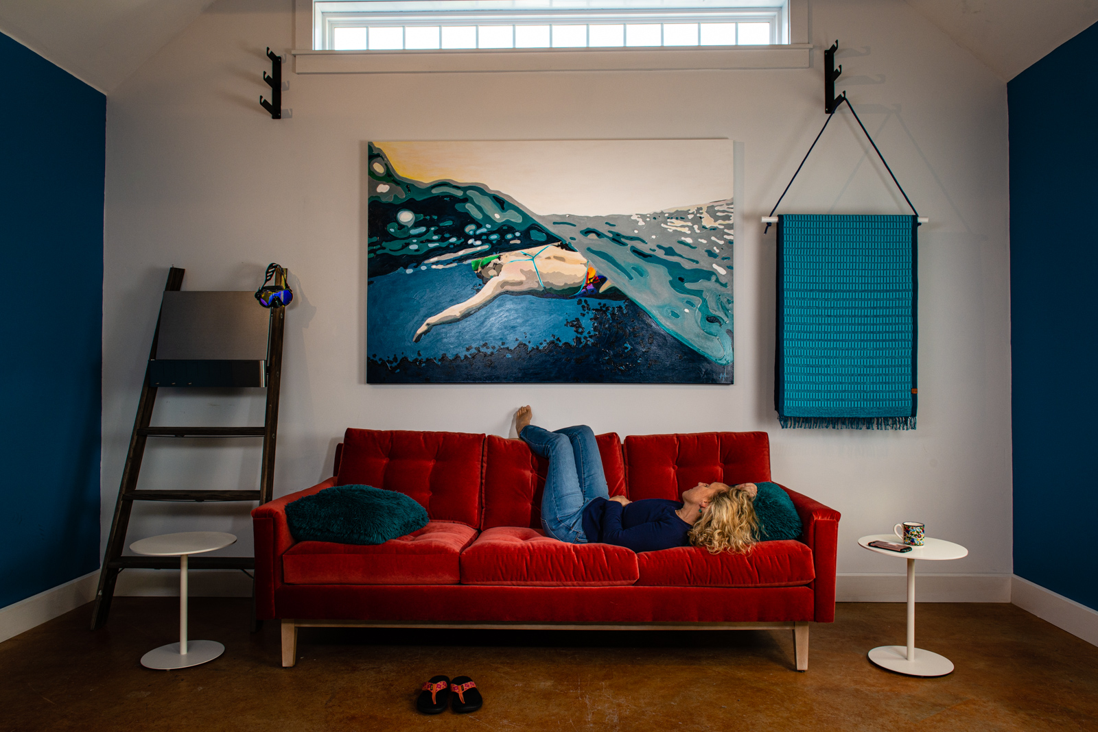 Heather Perry relaxing on a red velvety couch gazing at her paintings on the wall.