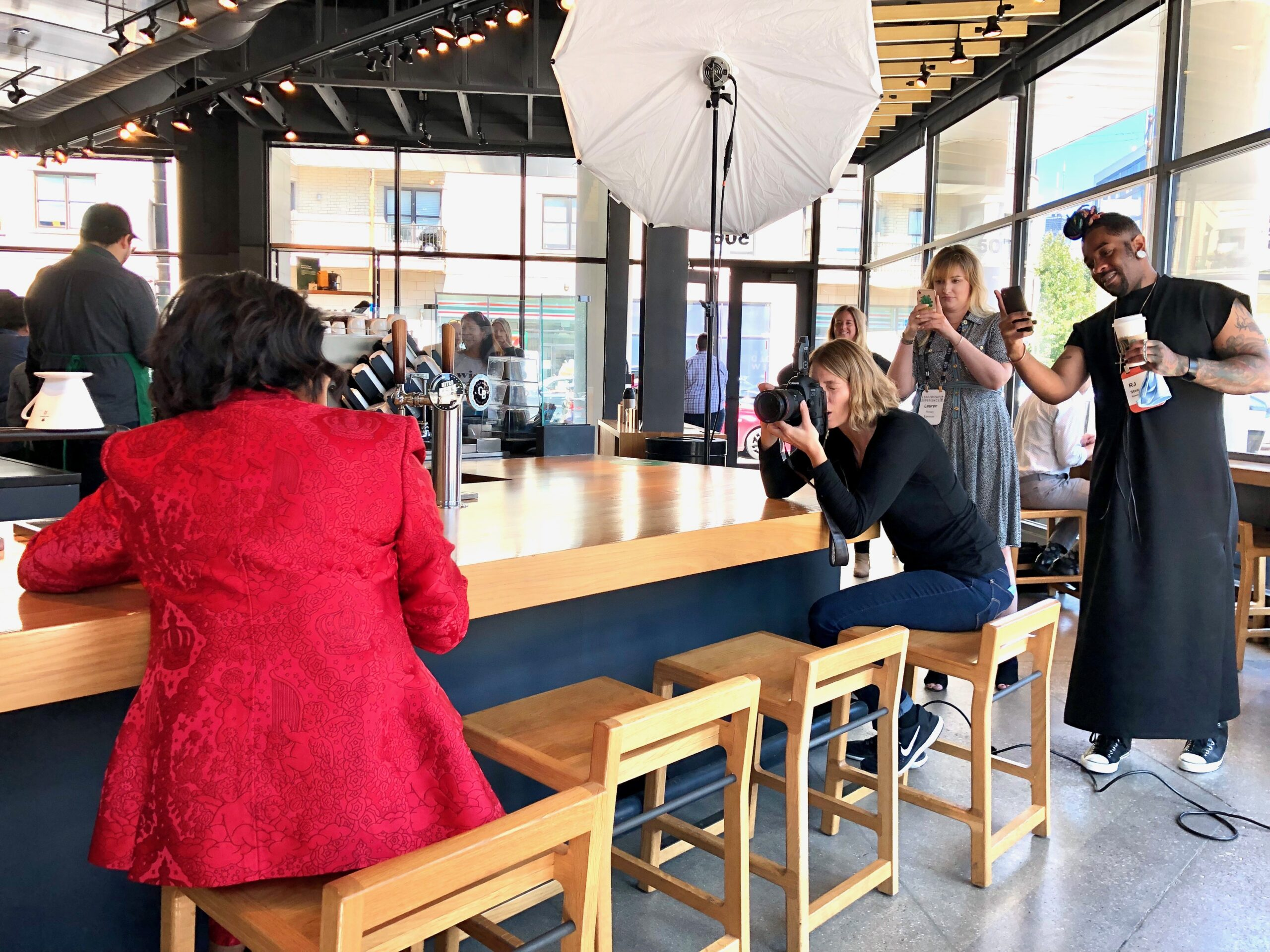 Crew members stand behind Sara Stathas as she photographs Roz while sitting at the counter at Starbucks