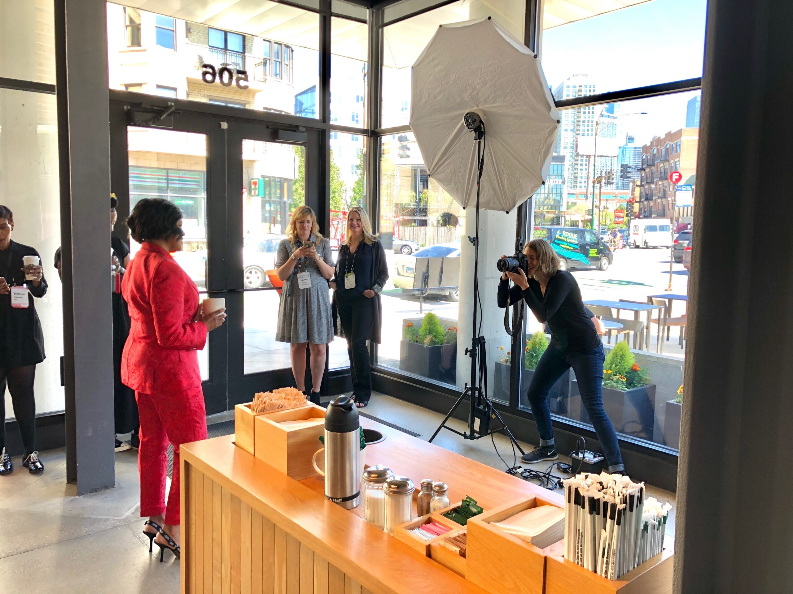Behind the scenes shot shows Sara Stathas as she photographs Starbucks COO Roz Brewer
