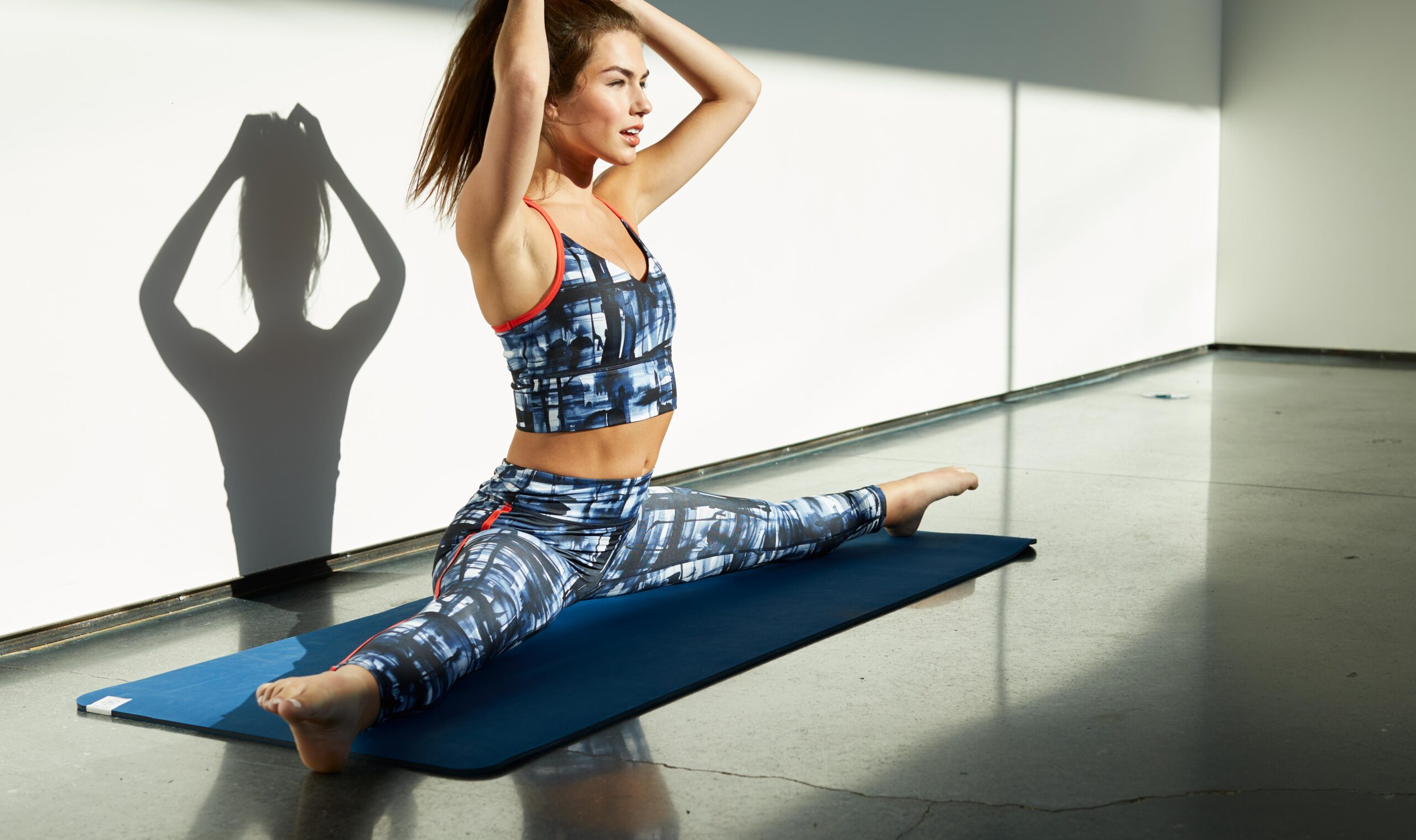 Jason Innes captures a model in yoga attire doing a side split on a yoga mat with her hands on her head