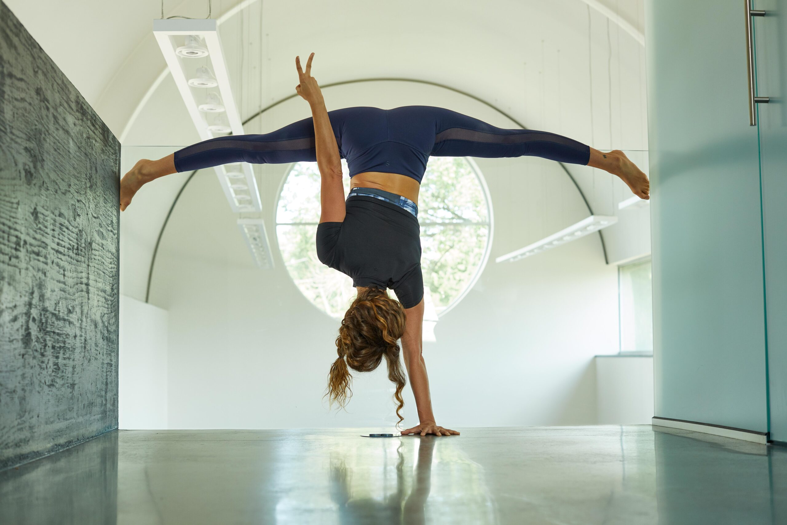 Jason Innes' photo of a model in a one-handed handstand with her legs split, while her other hand flashes a peace sign
