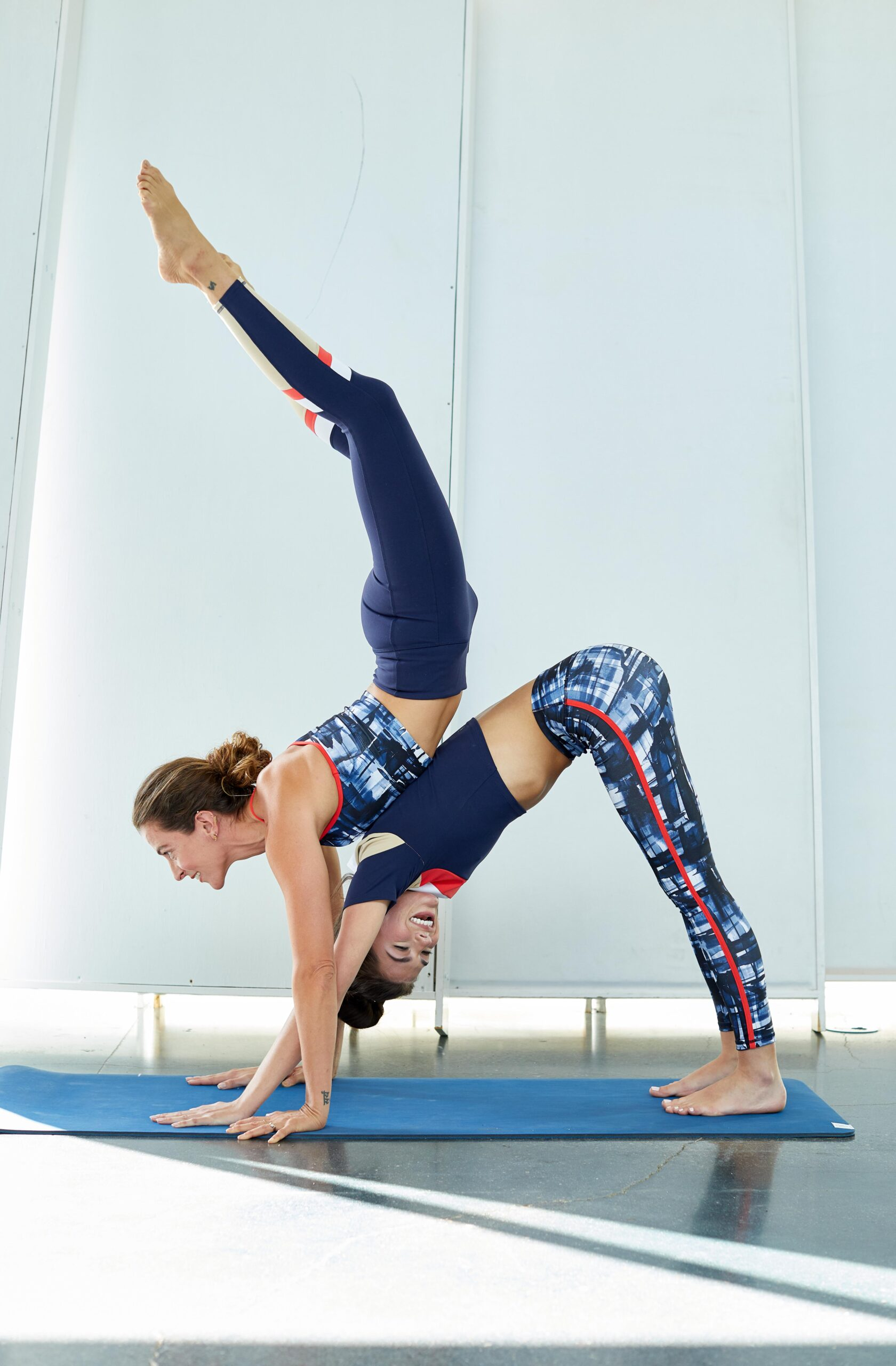 Jason Innes shows one model posed in downward dog and the other model doing a handstand, leaning against her back