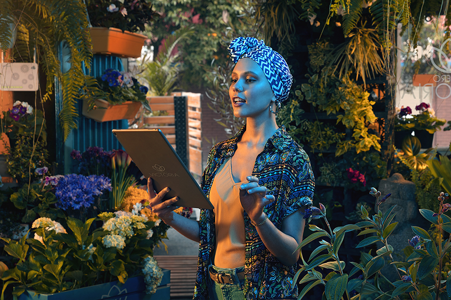 Jorge Oviedo photographs a woman in a headscarf surrounded by plant life as she scrolls on her screen for ETB