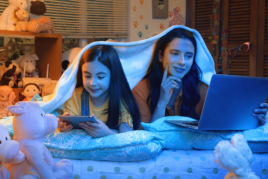 A younger girl and her sibling share a blanket while watching shows on a computer screen and tablet. Image shot by Jorge Oviedo for ETB.
