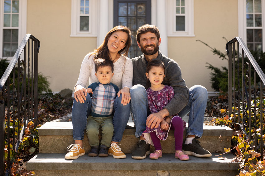 Josh Behan's COVID project Front Porchtrait shows a family with two young children sitting on their front steps together
