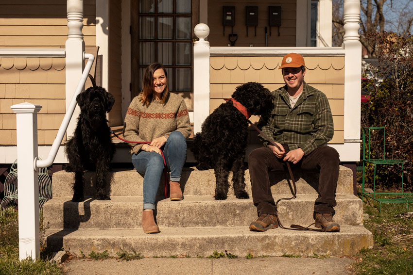 Josh Behan's COVID project Front Porchtrait shows a young man and woman sitting in front of their house with two black dogs