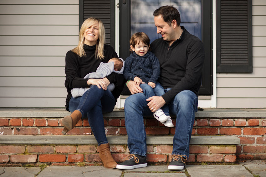 Josh Behan's COVID project Front Porchtrait shows smiling parents on brick steps with a toddler and newborn baby