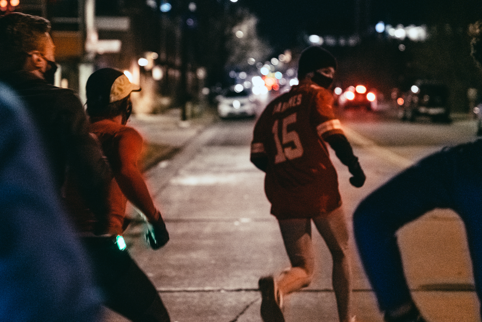Matt Trape photographs male runners in the dark as they turn on to a busy street for TTB in Denver