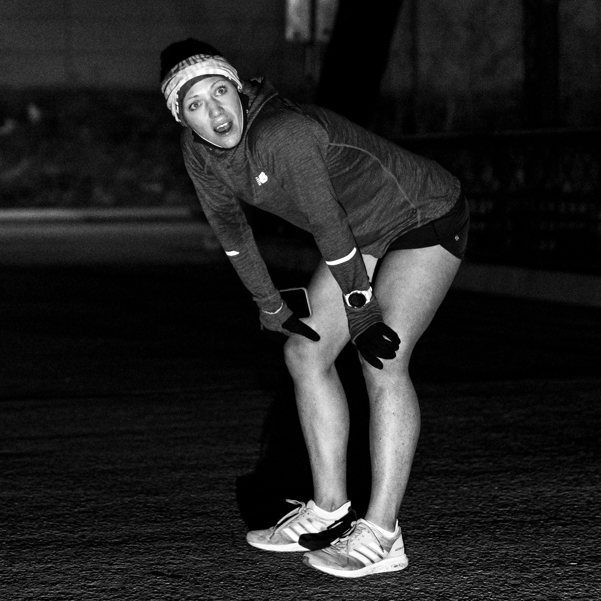 Matt trappe photographs runner bent over with hands on her knees looking completely out of breath and yet alert and full of adrenaline for Take the bridge in Denver