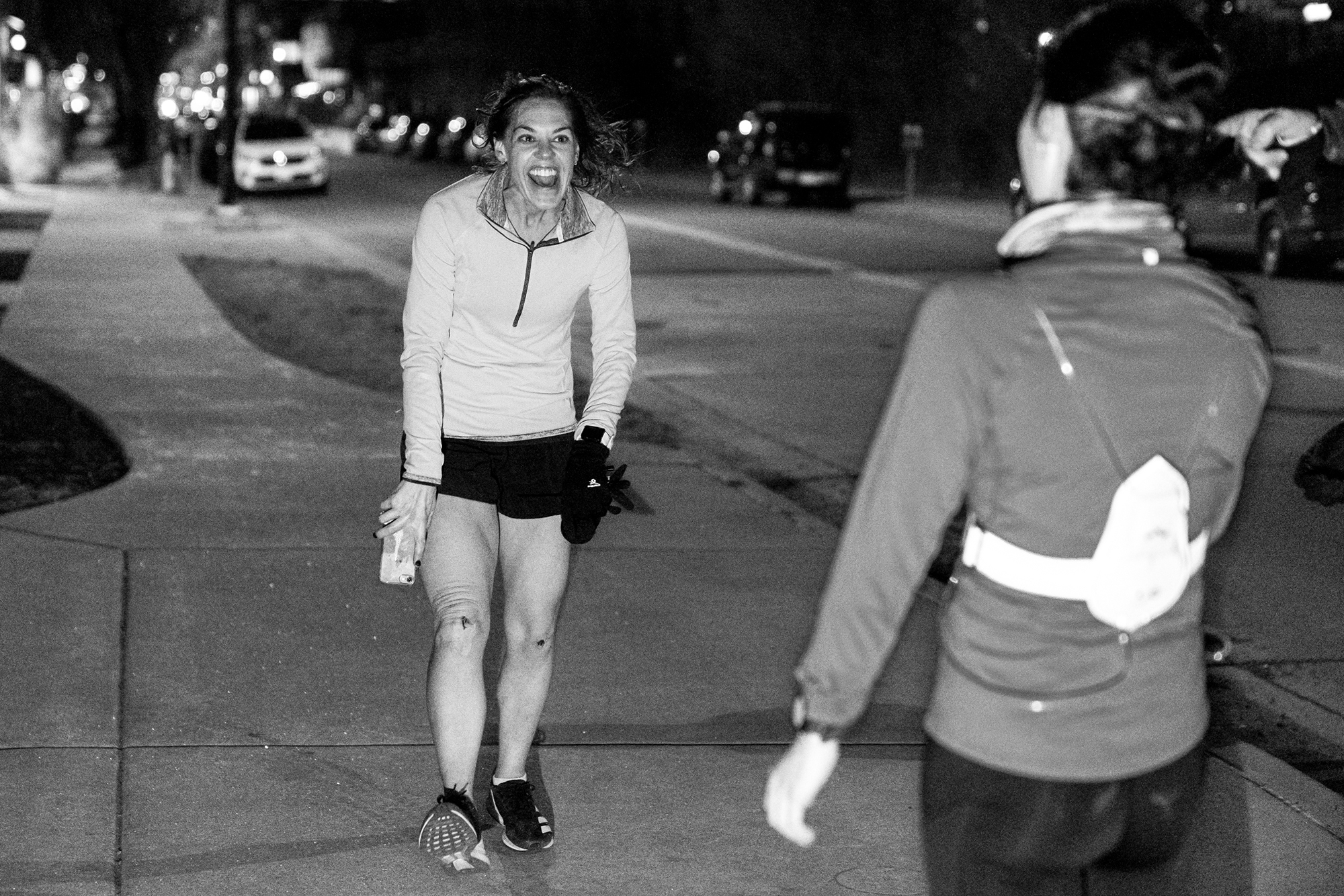 Matt Trappe photographs runner finished happy to see her friends with skinned knees and big grins for TTB in Denver