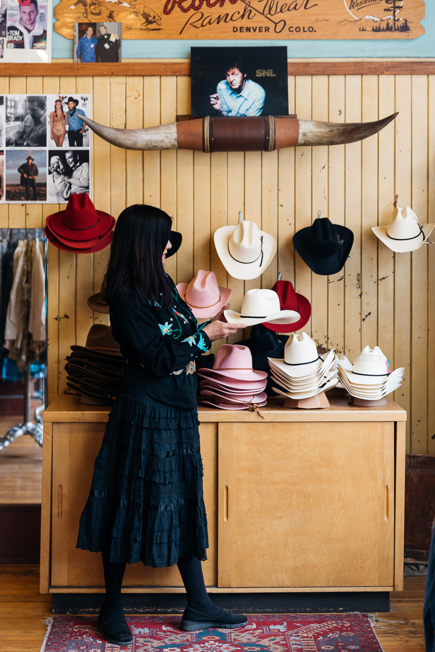 Photo shows a woman in black admiring a display of cowboy hats