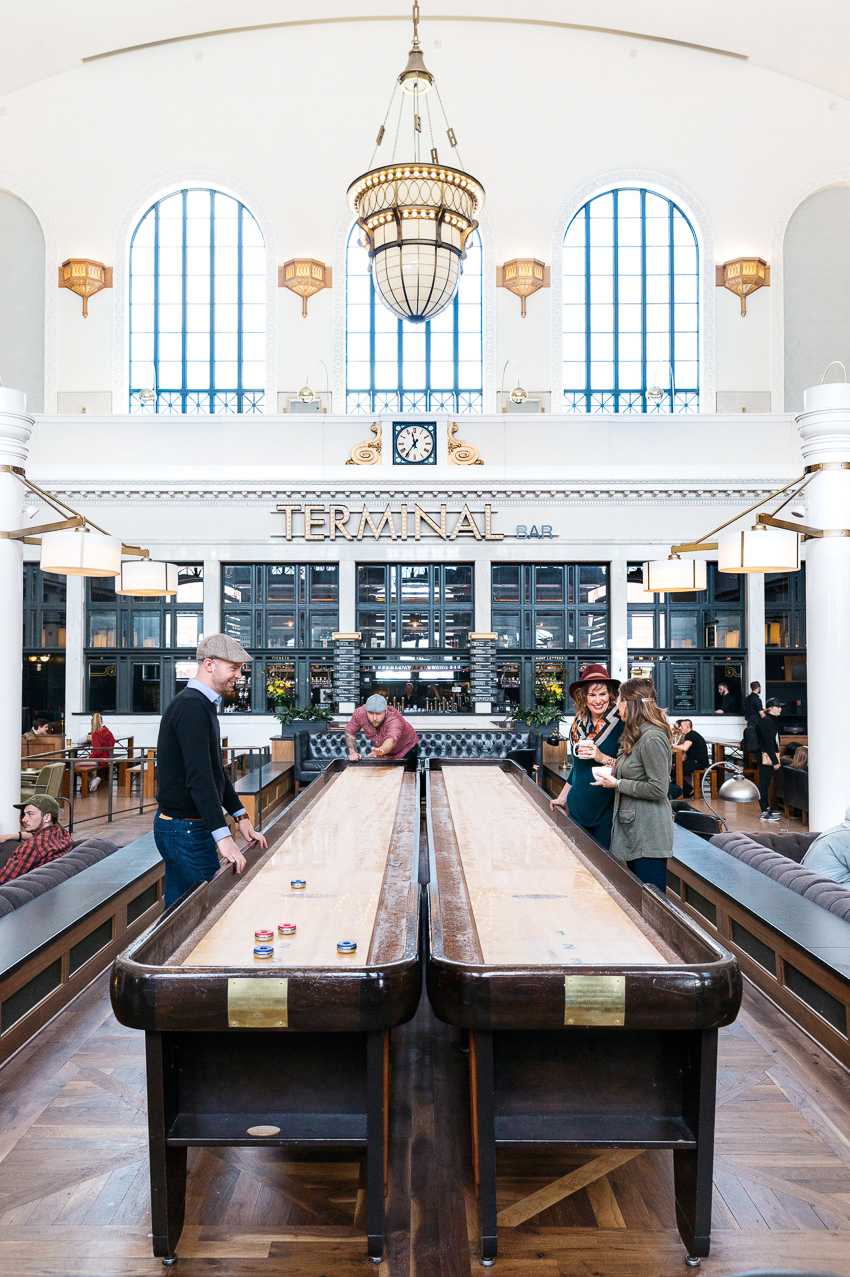 Rebecca Stumpf shoots several people playing shuffleboard outside of the Terminal Bar for Hemispheres