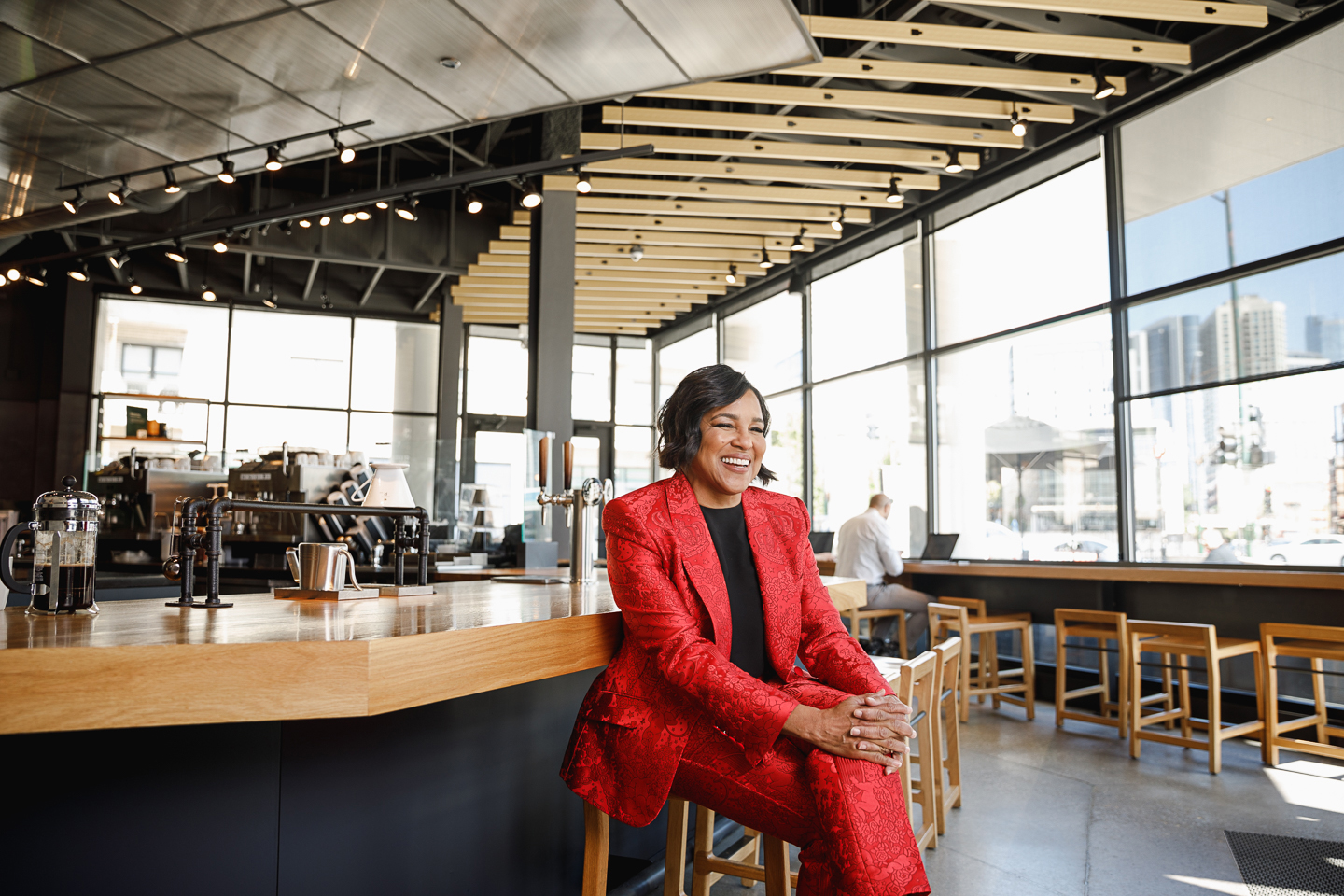 Sara Stathas' photo of Roz Brewer in a red suit, sitting with her legs crossed at the Starbucks counter