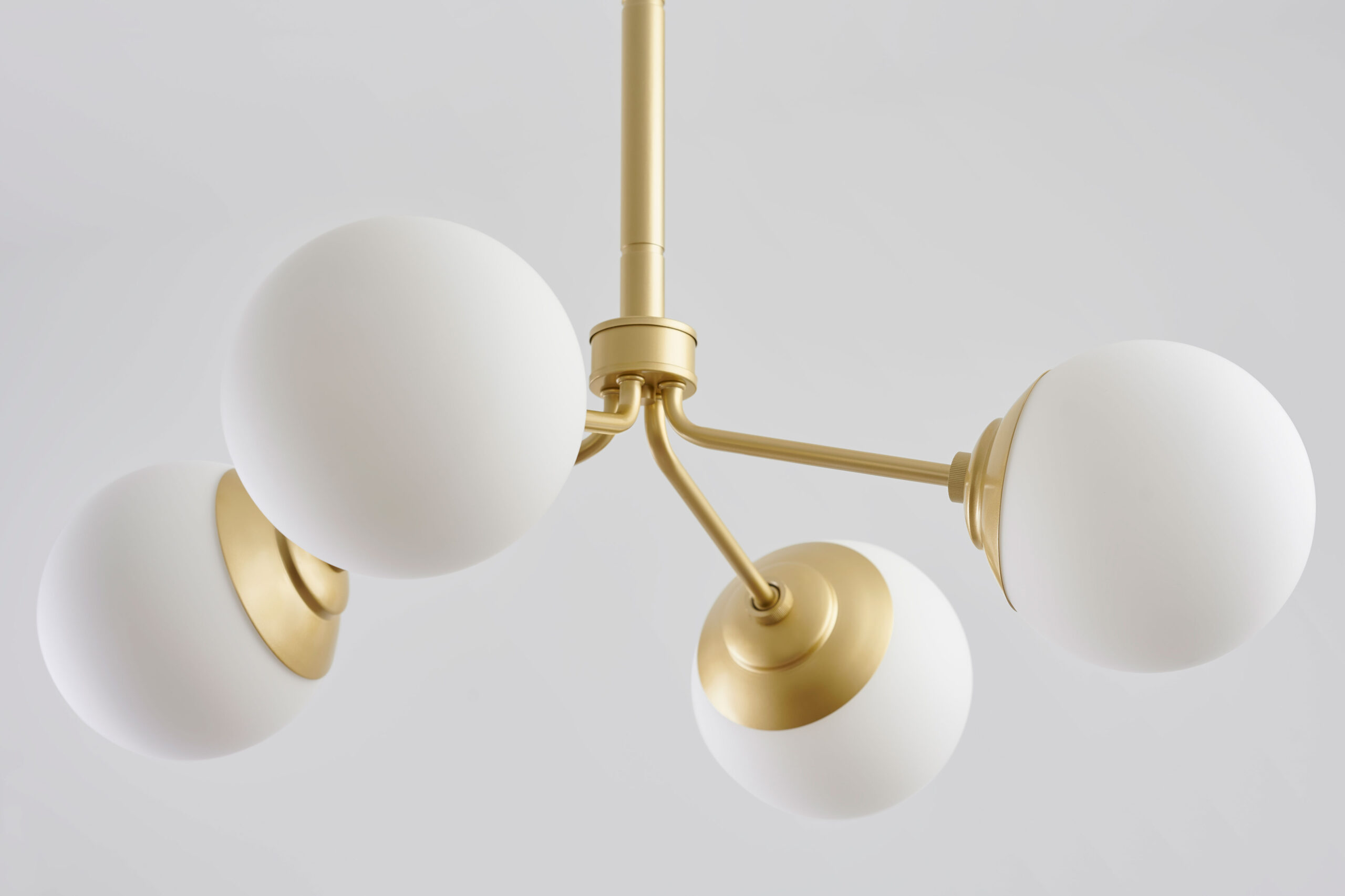 William DeShazer photographs elegant gold and white light fixture for Hunter Fan Company