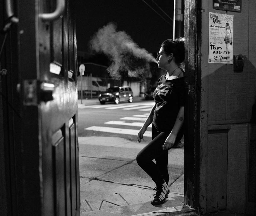 Patron smoking outside a Philadelphia dive bar by Gene Smirnov