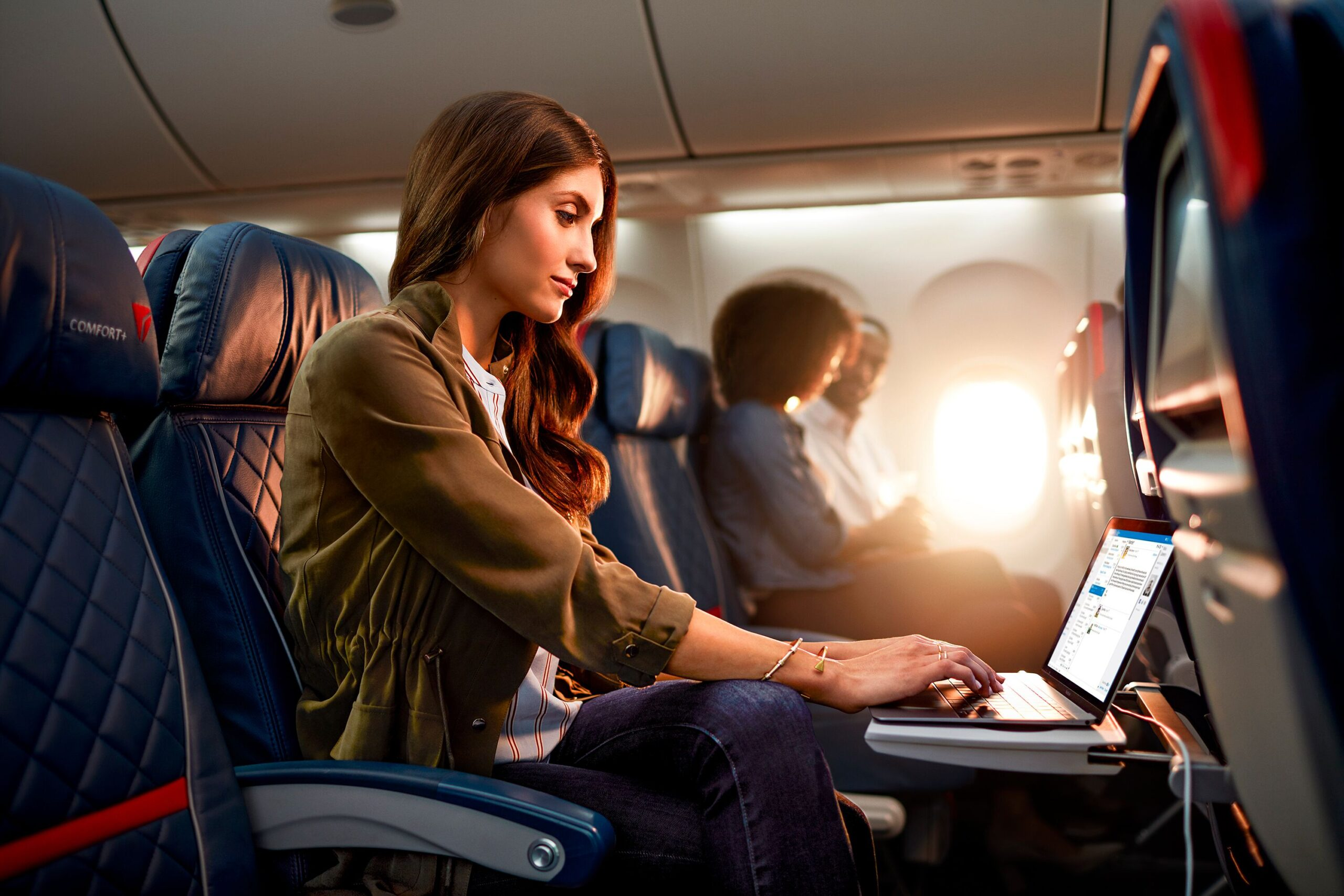 A young woman works on a laptop during her Delta flight as shot by John Fulton