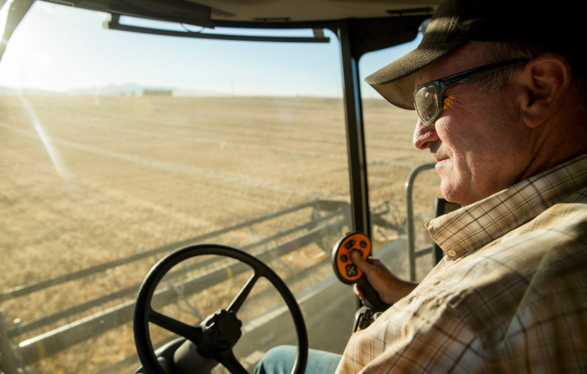 Farmer piloting a combine harvester shot by John Valls