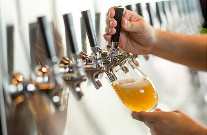 Barback pouring a craft beer by John Valls