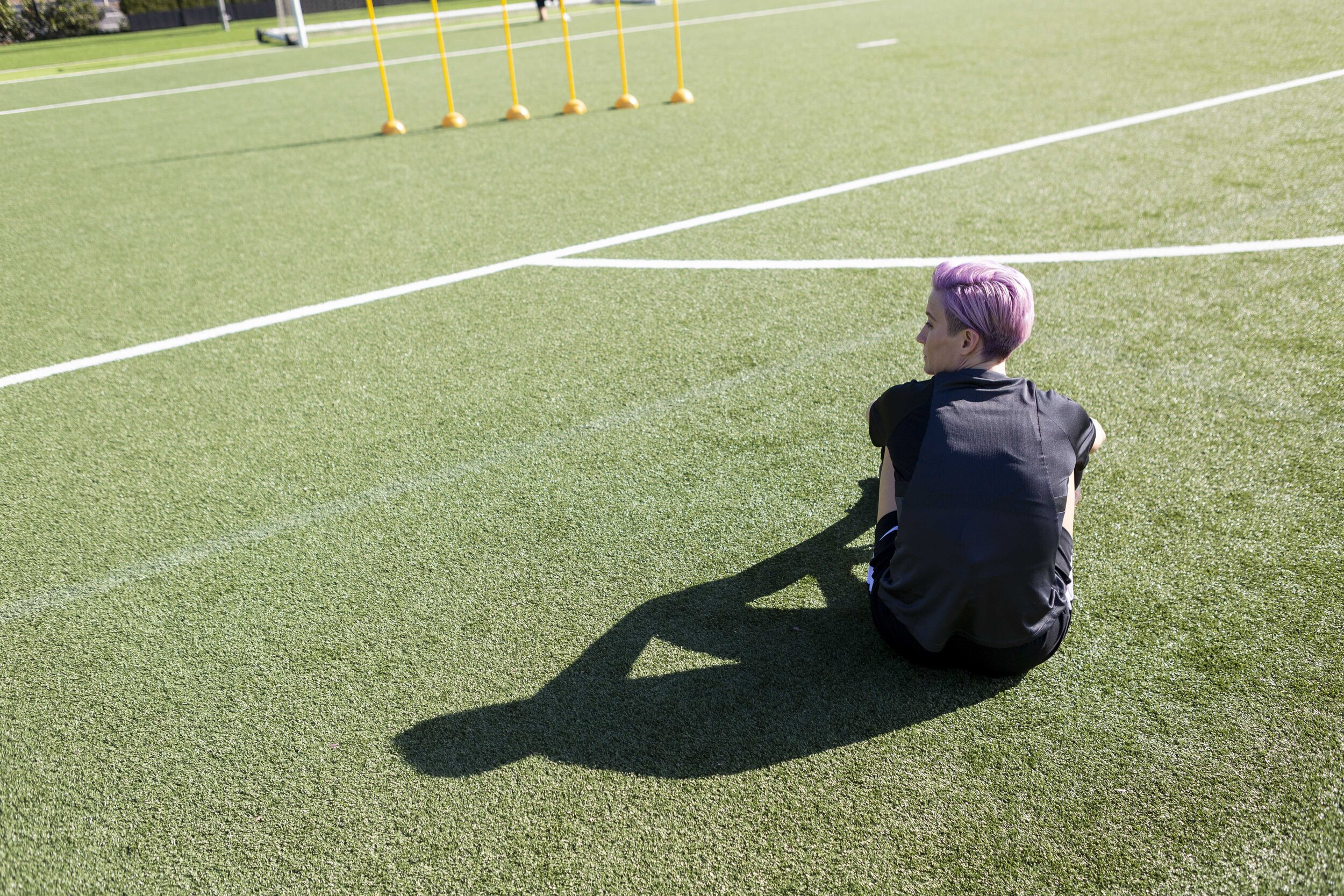 Sabrina Hill photographs Megan Rapinoe sitting on the green with her silhouette stretched out behind her in the late light for The Skills