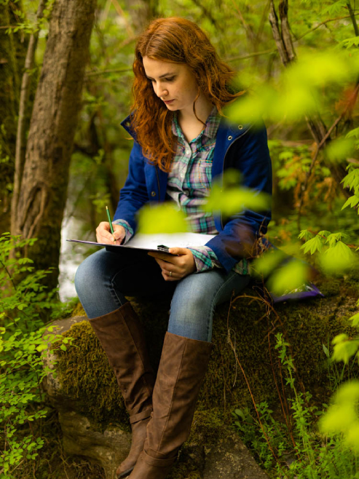 Woman drawing in a forested scene shot by Ed Sozhino for Case Knives