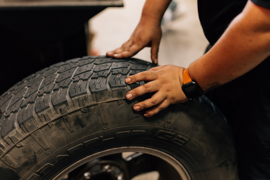 A man pushing a tire with greasy hands shot by Abigail Bobo for Caliber Collision