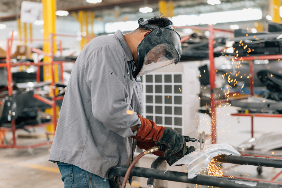 Sparks fly while a shop mechanic saws shot by Abigail Bobo for Caliber Collision