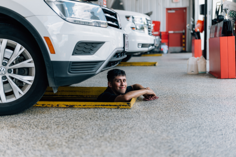 Mechanic peeking out from under a car shot by Abigail Bobo for Caliber Collision