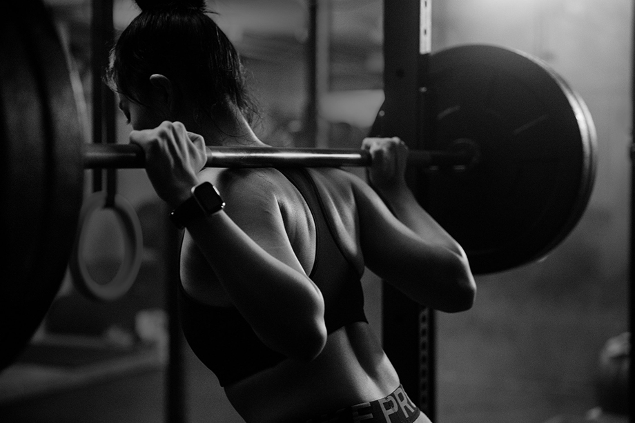 Image of Carrie Xu lifting weights taken from behind. Photographed by Albert Law.
