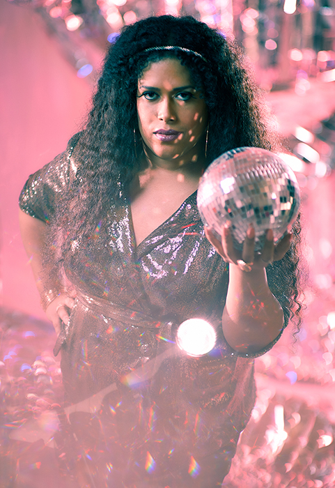 Fran Collazo holds a disco ball shot by Amy Rose Productions for Out and Out
