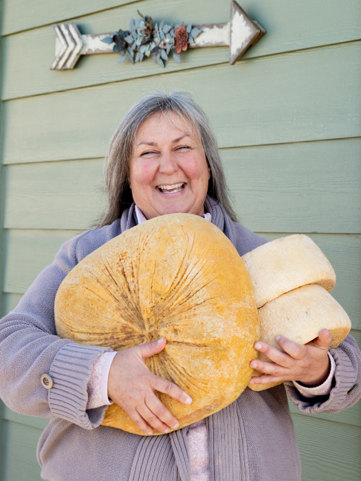 Woman happily holding three large wheels of cheese shot by Angela DeCenzo for National Geographic Traveller Food magazine