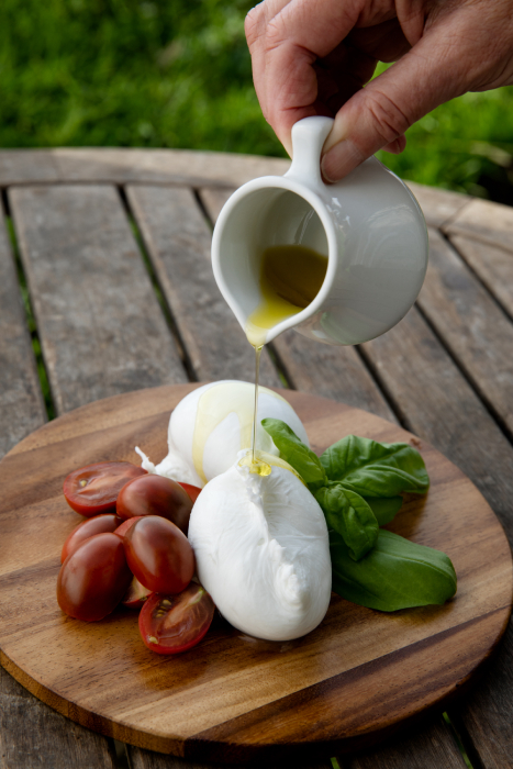 Olive oil being poured over fresh mozzarella, cherry tomatoes and basil shot by Angela DeCenzo for National Geographic Traveller Food magazine